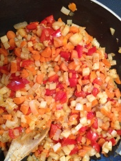 The potatoes, peppers, onion and carrots sautéing in the pan