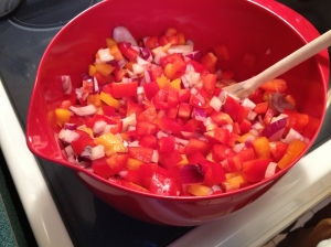 Diced red and yellow peppers as well as diced red onion are ready to be softened in the olive oil