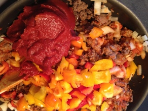 Sausages, peppers, tomato paste, tomato sauce, onions and other goodies are mixed with rice and stuffed into the peppers
